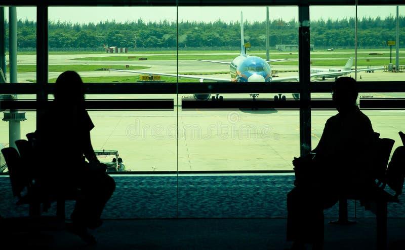 Passagerare som väntar på avvikelseporten för att stiga ombord flygplanet arkivbild