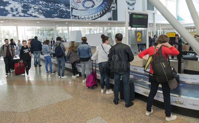 Passagerare som väntar på bagage på flygplats arkivfoto