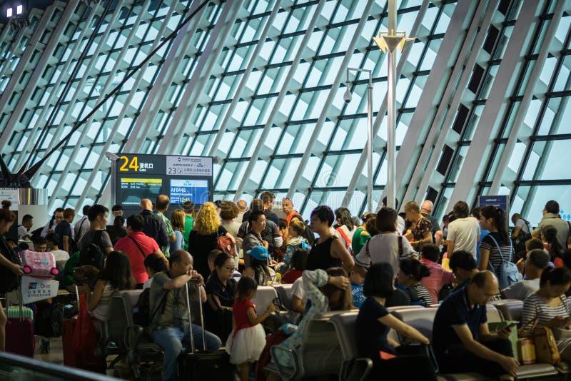 Passagerare som väntar på den fullsatta avvikelseporten efter fördröjning, Shanghai Pudong flygplats, Kina royaltyfria bilder