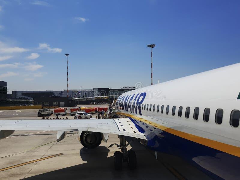 Passagerare stiger ombord på grov asfaltbeläggning av den Milan Bergamo flygplatsen, Italien royaltyfri bild