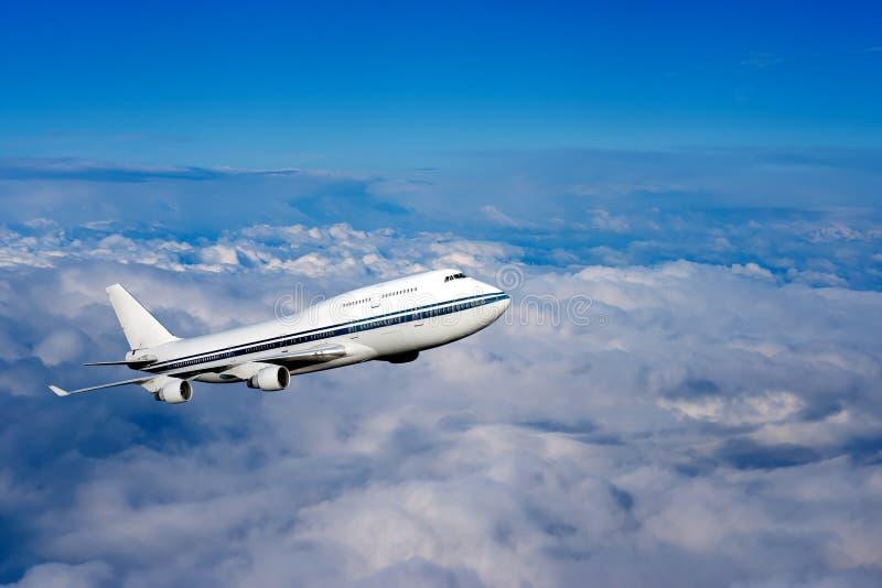 Passagerareflygplan i molnen fotografering för bildbyråer
