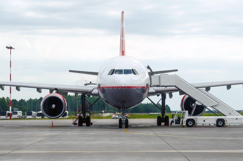 Passagerareflygplan i parkeringen på flygplatsen med en framåt näsa och en landgång arkivbild