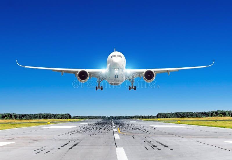 Passagerareflygplan med ljusa landningljus som landar på i bra klart väder med en blå himmel på en landningsbana royaltyfri bild