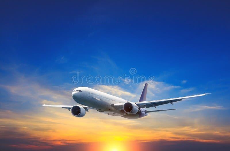 Passagerareflygplanflyg ovanför nattmoln och fantastisk himmel på solnedgången royaltyfri bild