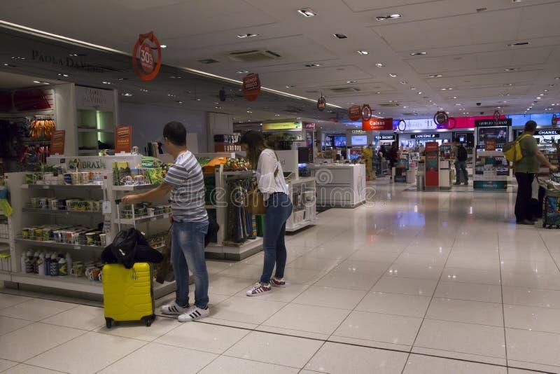Passagerareköpsouvenir i den tullfria flygplatsen shoppar arkivfoto