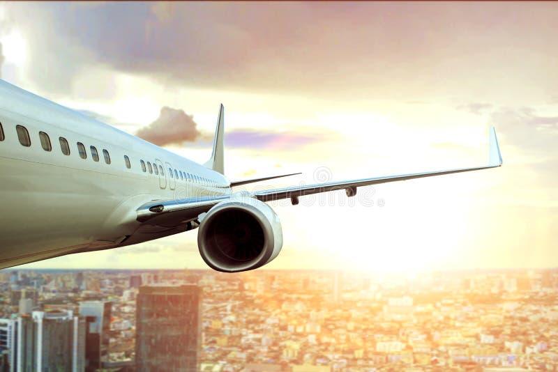 Passagerarenivån som flyger över stadsbyggnad, och solen tänder på backg fotografering för bildbyråer