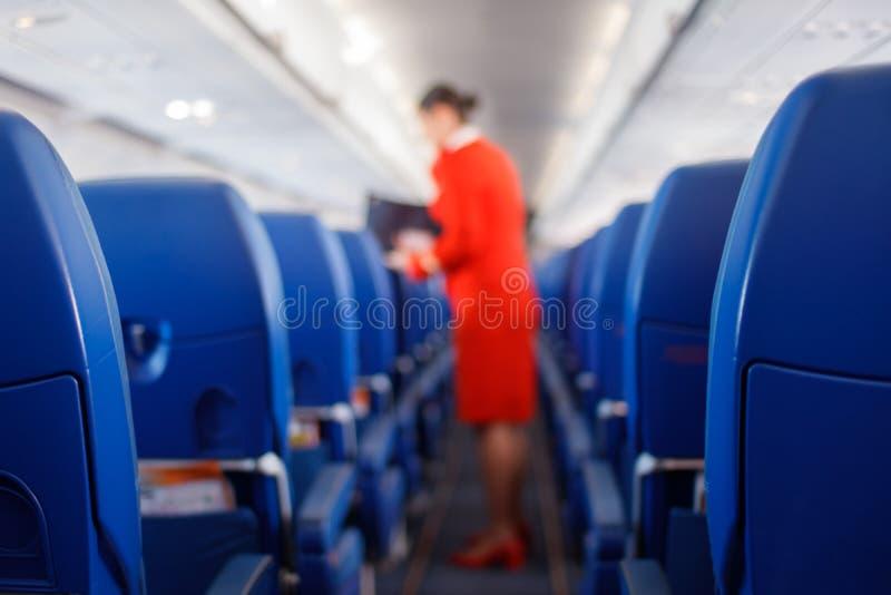 Passagerareplats i flygplan, inre av flygplanet och stewardessbakgrund Stewardessen framför service för passagerare royaltyfria bilder