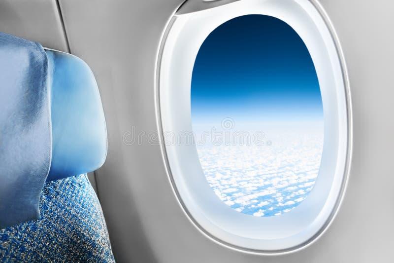 Passagerareplats i flygplan- och fönstersikt av himmel med moln royaltyfria foton