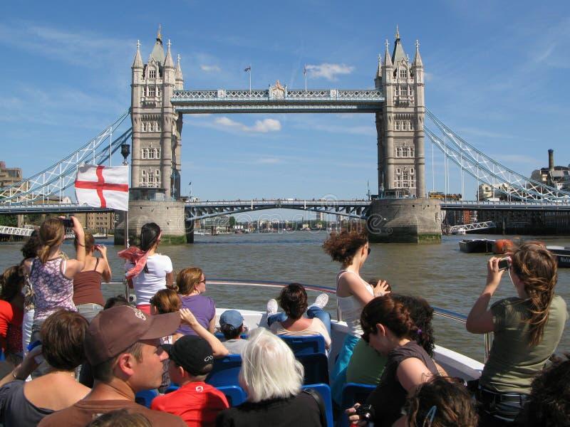 Passagerarna på kryssningfartyget på flodThemsen ser och fotografiet av tornbron i London, UK arkivfoto