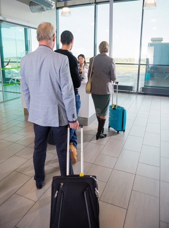 Passagers avec des sacs de chariot attendant à la réception d'aéroport photographie stock