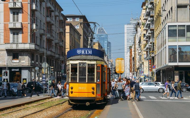 Passagers embarquant un tramsway jaune traditionnel à un centre de la ville occupé images libres de droits