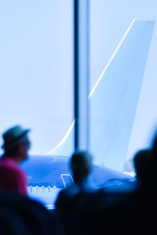 Passagers marchant en aéroport, vue de l'intérieur du regard à l'avion et ciel bleu images stock