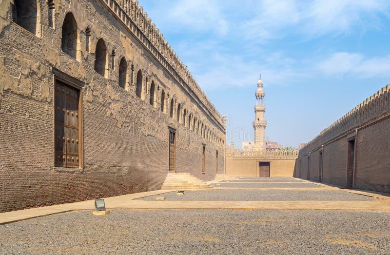 Passages die Ibn Tulun-moskee met minaret van Amir Sarghatmish-moskee bij verre afstand, Middeleeuws Kaïro, Egypte omringen stock afbeelding