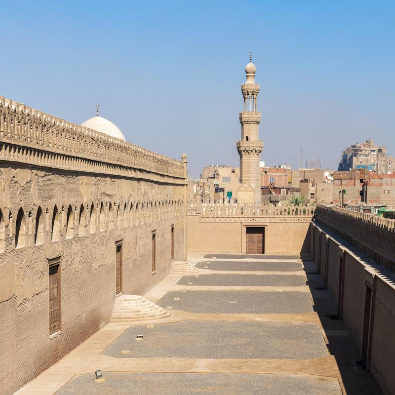 Passages outside Ibn Tulun mosque with the minaret of Amir Sarghatmish mosque at far distance, Cairo, Egypt stock image
