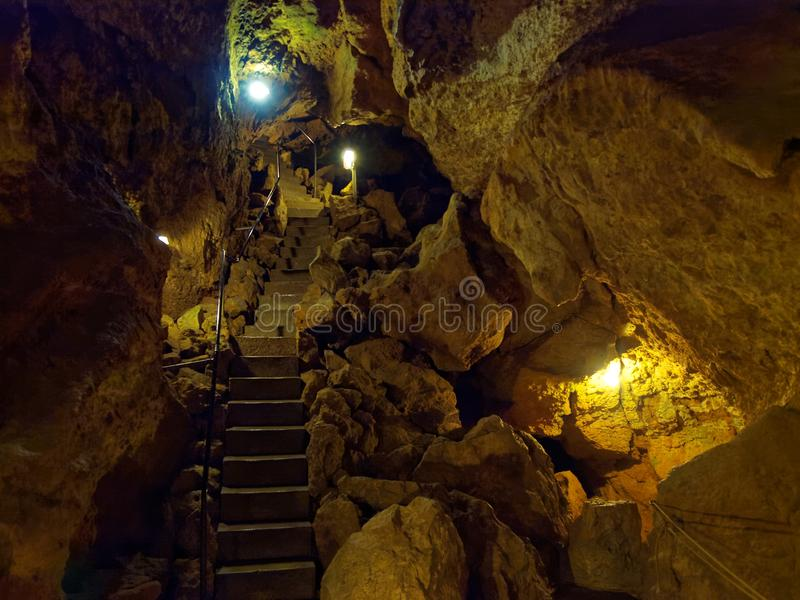 Passageway inside a pit cave with lights on stock photo