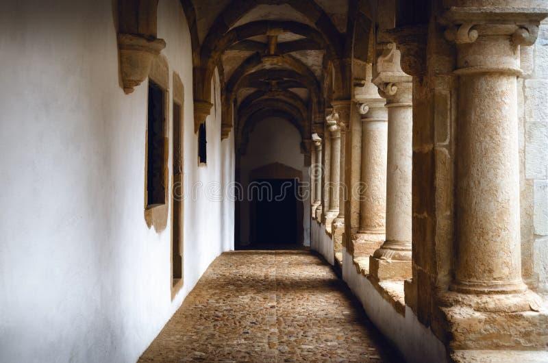 Passagge através de um claustro medieval antigo com parede branca e as colunas de pedra fotos de stock royalty free