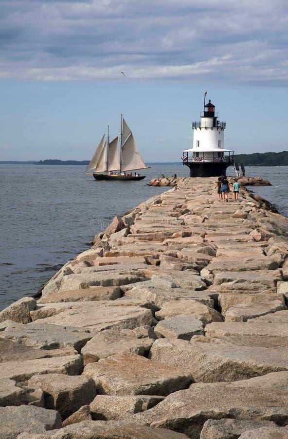 Passaggi della barca a vela dal faro sul bordo del frangiflutti in Maine immagine stock libera da diritti