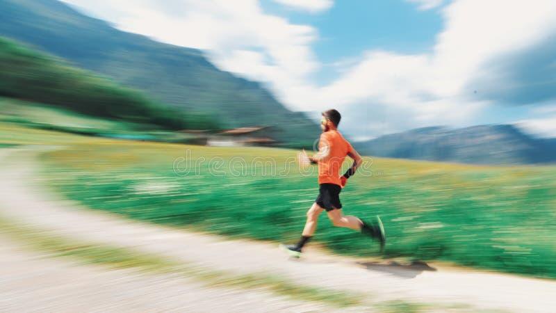 Passaggio del corridore nelle montagne in primavera con sfuocatura immagine stock libera da diritti