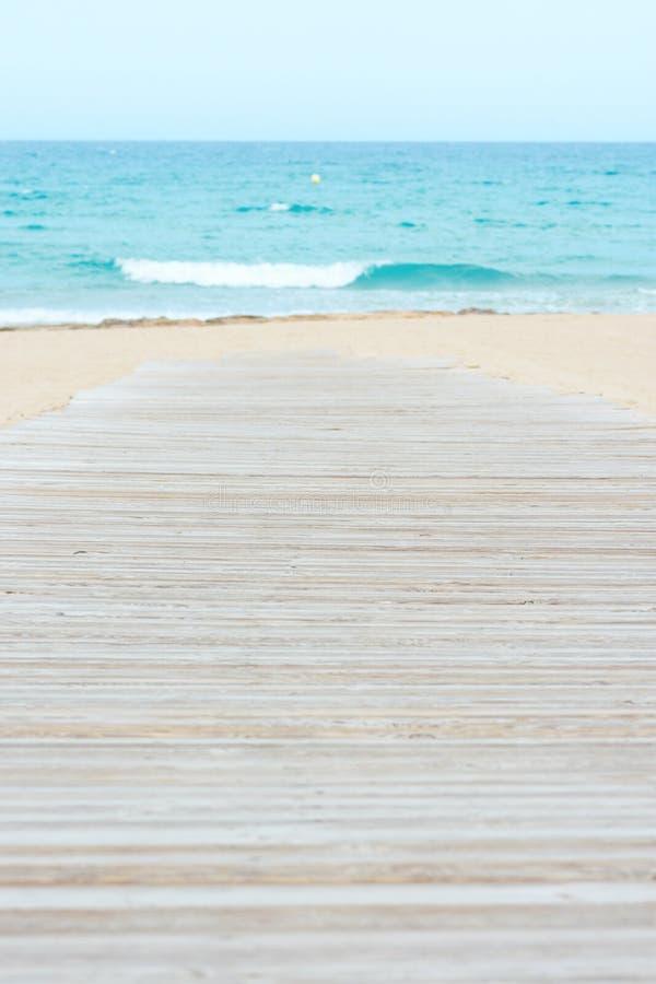 Passaggio pedonale di legno della plancia sulla spiaggia con il mare bianco del turchese della sabbia con le onde ed il cielo blu fotografia stock libera da diritti