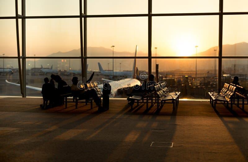 Passagier, der in einem Lobbyflughafenwarteflug im silho sitzt lizenzfreies stockfoto