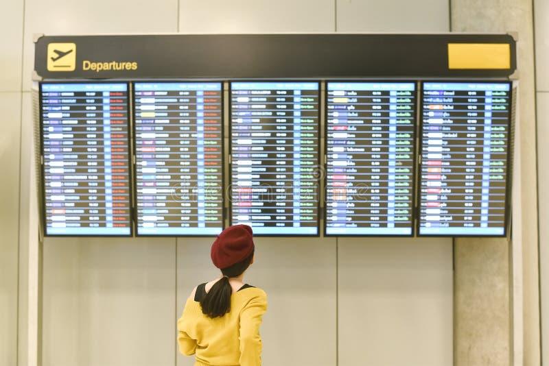 Passagier die vluchtstatus controleren bij de vertoning van de luchthaveninformatie stock foto