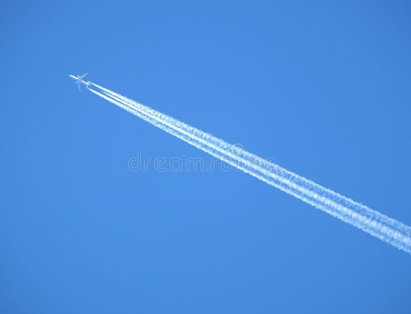 Passagier het straal vliegen in duidelijke blauwe hemel, die witte sleep verlaten stock afbeelding