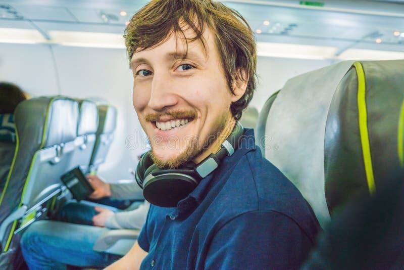 Passagier in vliegtuig die hoofdtelefoons met behulp van mens in vliegtuigcabine liste stock foto