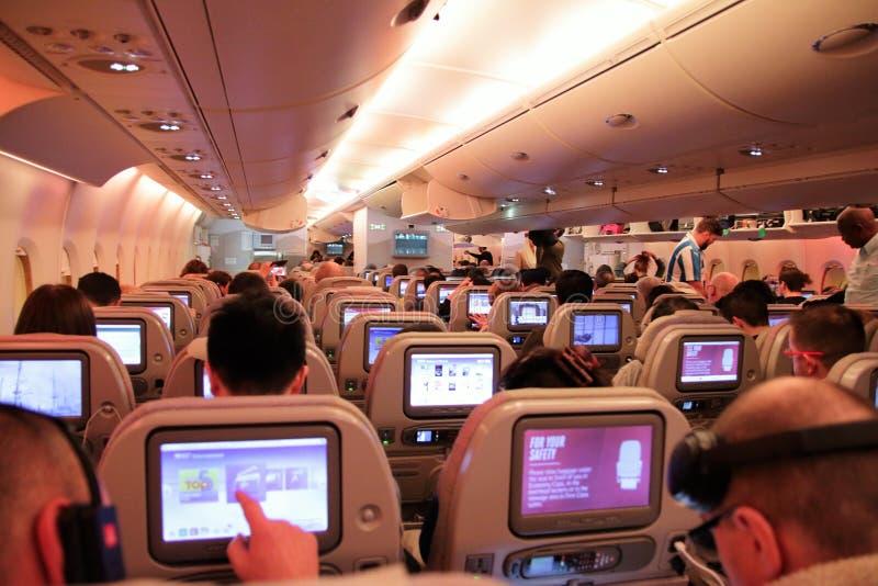 Passagiere auf einem Wirtschaftsflug, der die Sitze und die Touch Screens zeigt lizenzfreies stockfoto