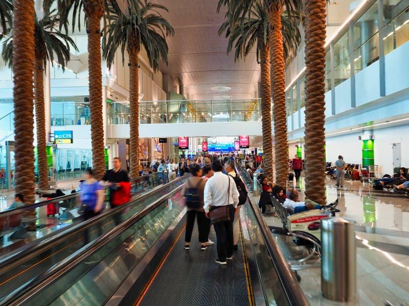 Passagiere, die in Abfahrt-Bereich, Dubai International-Flughafen, UAE warten lizenzfreie stockfotografie