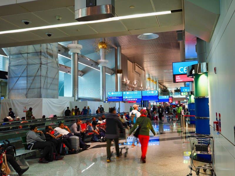 Passagiere, die in Abfahrt-Bereich, Dubai International-Flughafen, UAE warten stockfotografie