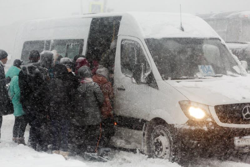 Passagiere, die auf öffentlichen Transportmitteln - Handelsstadtkleinbus während des schweren Winterblizzards verschalen stockfotografie