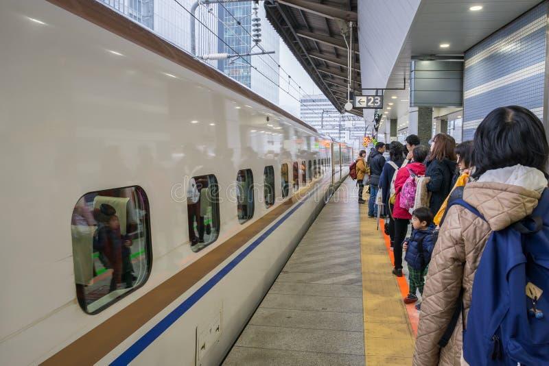 Passagiere, die auf Shinkansen-Kugelzug an Bahnhof Tokyos warten stockbild