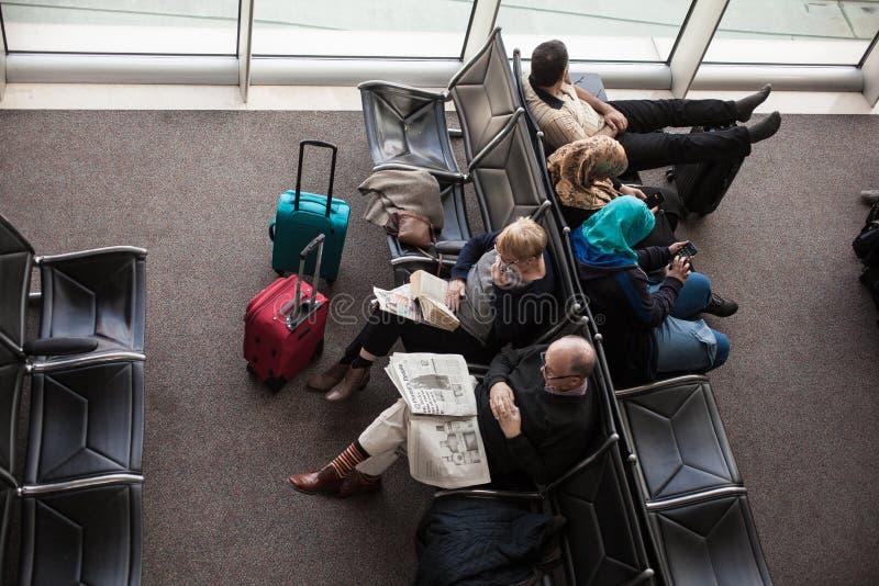 Passagiere im Flughafenwarteraum stockbild