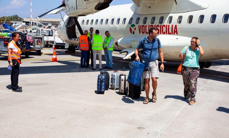 Passagiere mit Gepäck nahe bei dem Flugzeug stockfotografie
