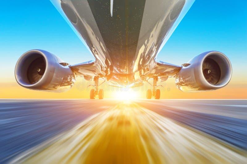Passagierflugzeug beschleunigt sich an der Hochgeschwindigkeitsansicht von unterhalb mit hellem Licht lizenzfreie stockfotos