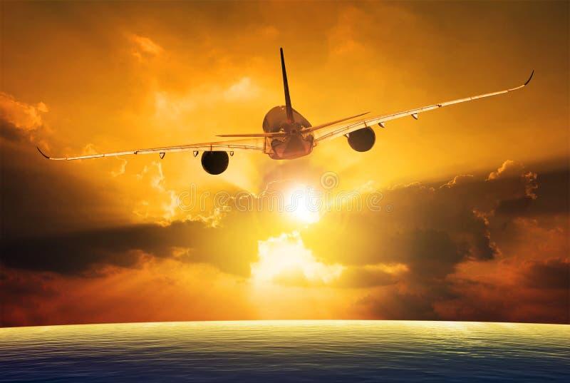 Passagierflugzeug, das über schönen Sonnenunterganghimmel fliegt stockbild