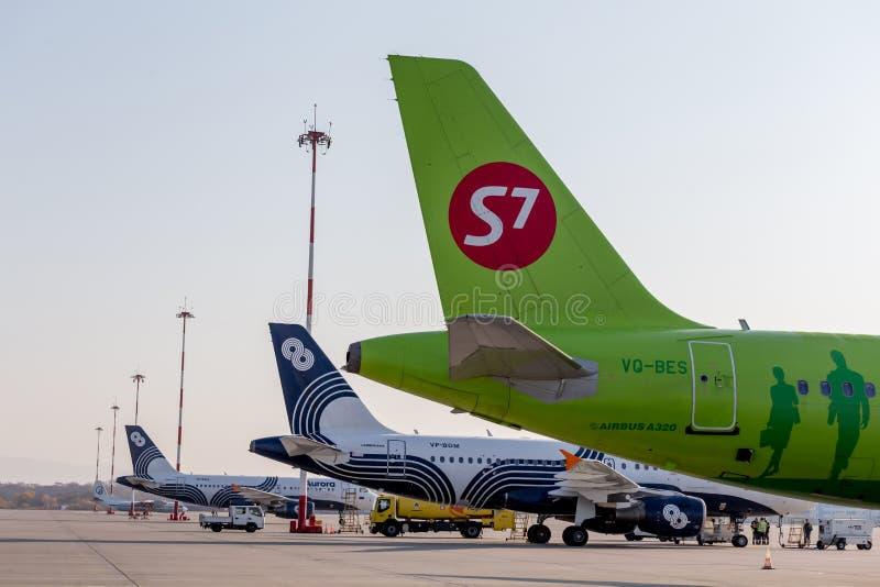 Passagierflugzeuge von S7 Airlines und von Aurora Airlines auf Flugplatz Flugzeugrümpfe Luftfahrt und Transport lizenzfreie stockfotografie