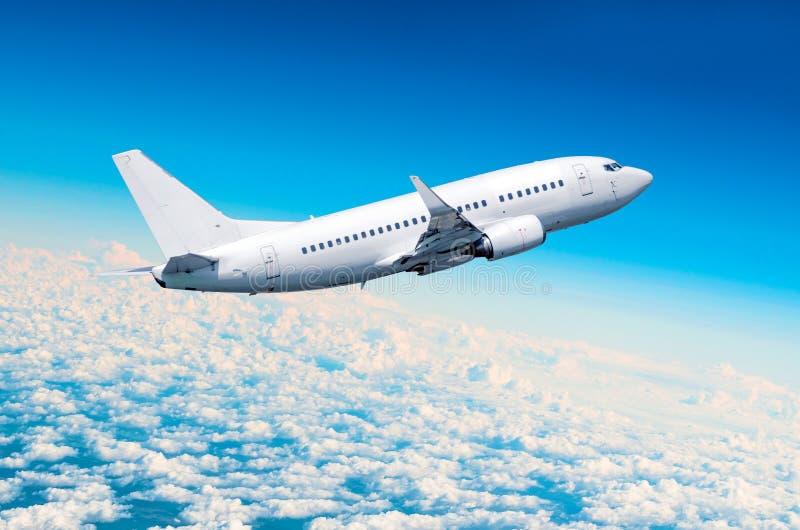 Passagierflugzeugfliege auf einer Höhe über bewölkten Wolken und blauem Himmel lizenzfreie stockbilder