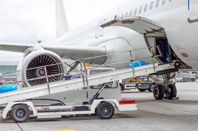 Passagierflugzeugladen des Gepäckes in den Laderaum am Flughafen stockbilder