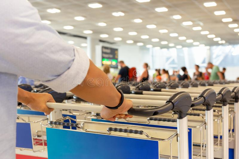 Passagierhand auf Gepäckwarenkörben im Flughafen lizenzfreie stockfotos