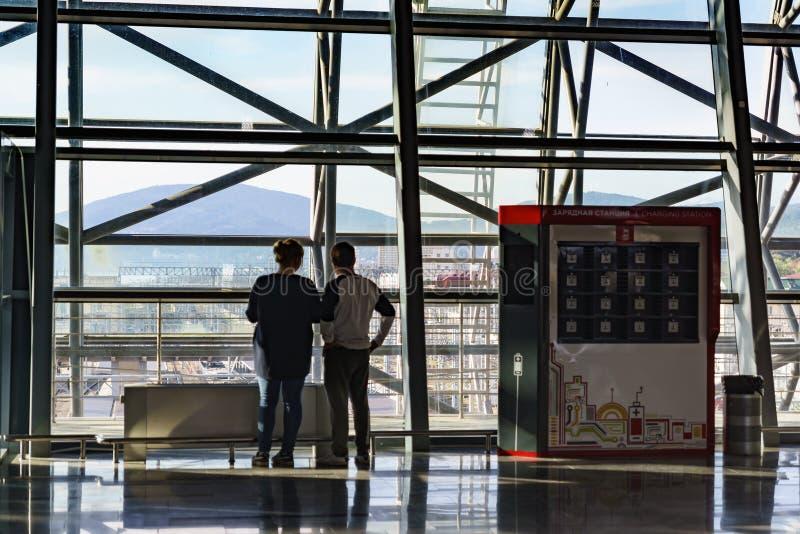 Passagiers bij het venster in de wachtkamer van een groot modern station Installatie voor het laden van mobiele telefoons en stock foto's
