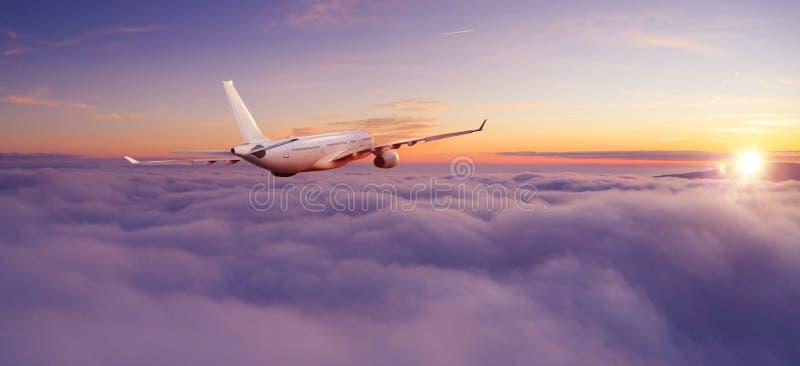 Passagiers commercieel vliegtuig die boven wolken vliegen stock afbeeldingen