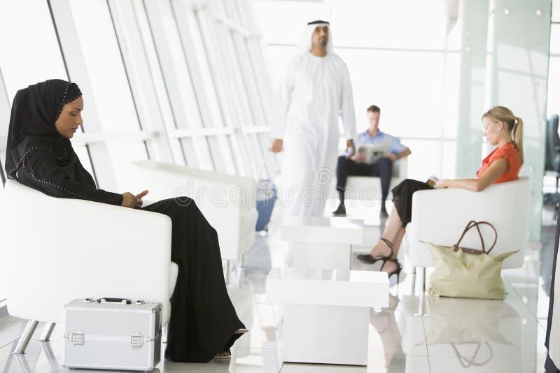 Passagiers die in de zitkamer van het luchthavenvertrek wachten stock fotografie