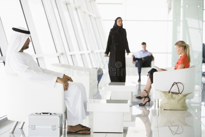 Passagiers die in de zitkamer van het luchthavenvertrek wachten stock afbeelding