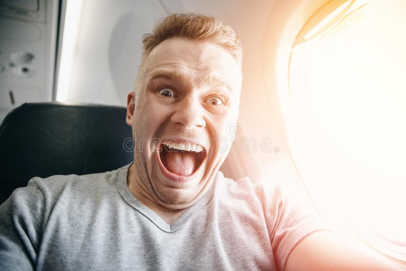 Passagiersmens in vliegtuigkoppelingen zijn hoofd, bang van hoogten en vlucht Schreeuw en schreeuwuitdrukking royalty-vrije stock foto's