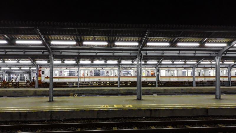 Passagiersplatform bij nacht bij het de stadsstation van Djakarta Station bij nacht stock afbeelding