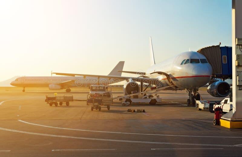 Passagiersvliegtuig in de luchthaven bij zonsopgang stock foto