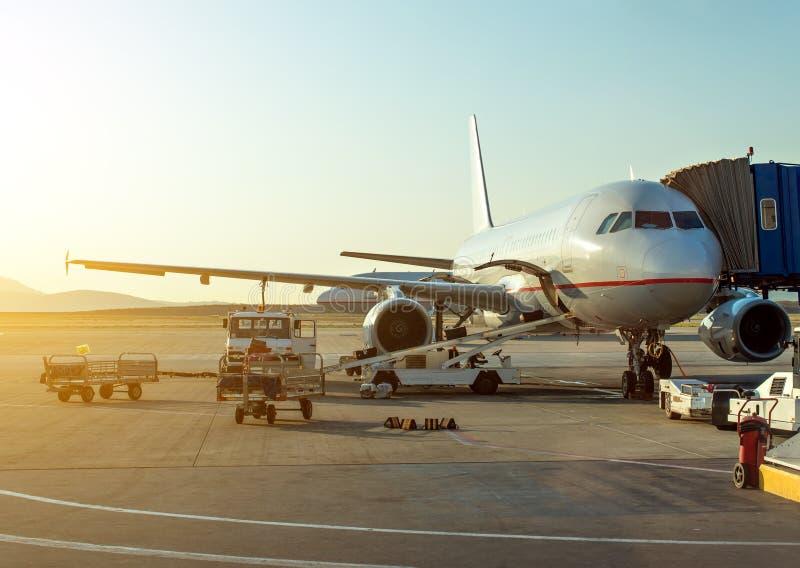 Passagiersvliegtuig in de luchthaven bij zonsopgang stock fotografie