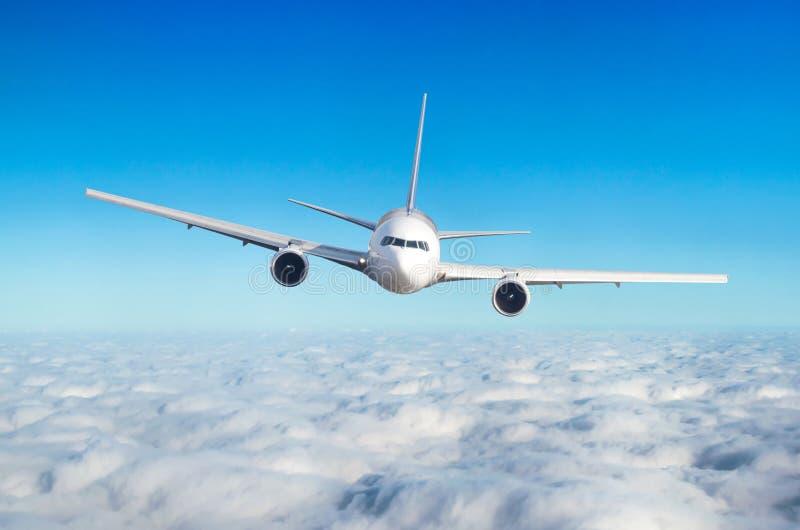 Passagiersvliegtuig die bij vliegniveau hoog in de hemel boven de wolken vliegen Mening direct vooraan, precies royalty-vrije stock afbeeldingen