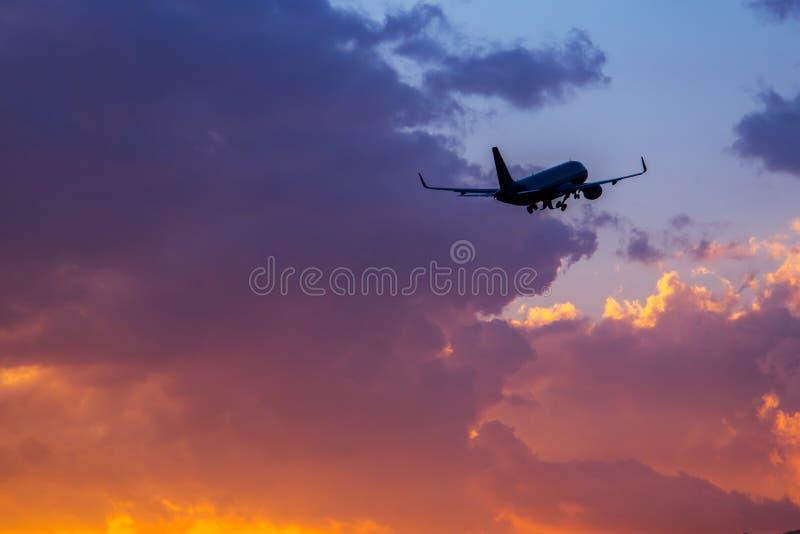 Passagiersvliegtuig die in de hemel bij zonsondergang vliegen stock foto's